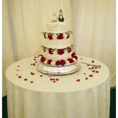 Three tier wedding cake with red roses and character tops