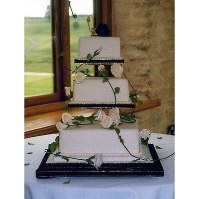 Three tier cake with white flowers and stems draped over cake