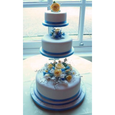 Three tier cake with blue ribbon trim and white and blue flowers on each tier