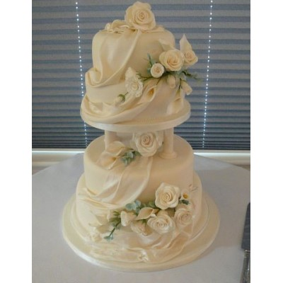 Highly decorated four tier cake with flowers and sheet style drape design
