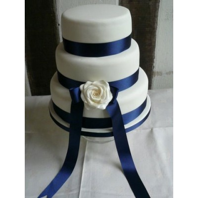 Three tier cake with blue ribbon and white flower