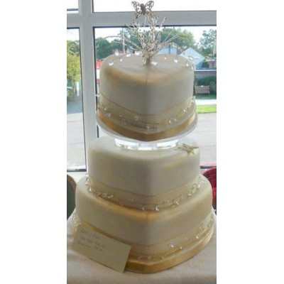 Three tier wedding cake with gold trim and topper