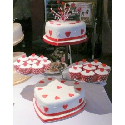 Heart shaped red and white wedding cake with cupcake sides