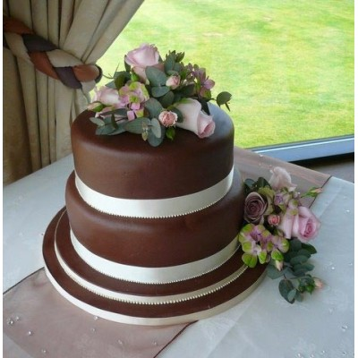 Chocolate coloured wedding cake with flowers and ribbon surround