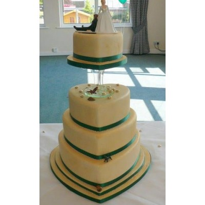 Four tier cake with bride and groom characters on top