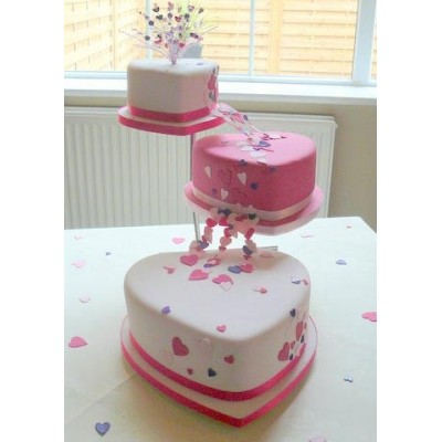 Three tier heart shaped wedding cake in white and pink.