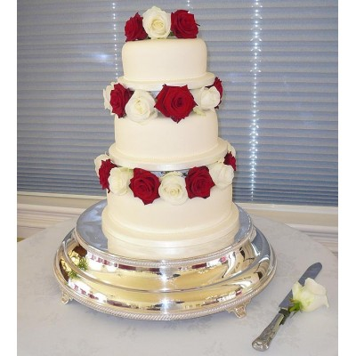 White cake with red and white roses in between layers