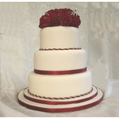 Classic white cake with red roses and ribbon