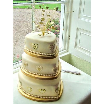 Three tier cake with gold heart design and crystal topper