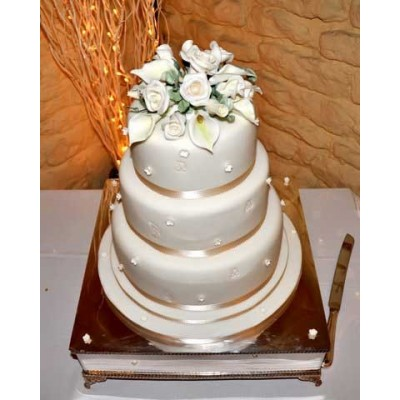 Three tier cake with white flowers and gold ribbon trim