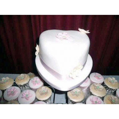 Heart shaped cake in white with cupcakes