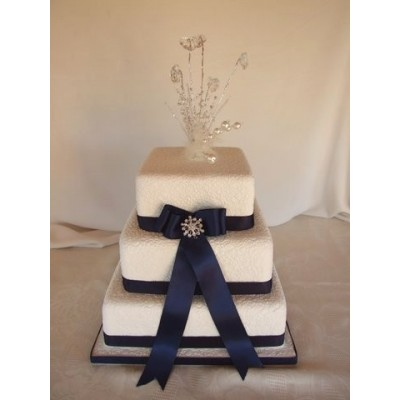 White three tier cake with blue ribbon and crystal topper