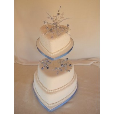 Heart shaped three tier cake with blue details and crystal toppers