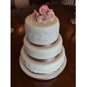 Three Tier Wedding Cake With Flowers and Pink Detailing
