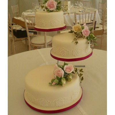 3 individual tiers of cake with piped border and sprays of roses and ivy