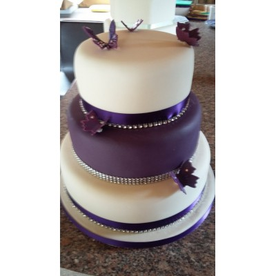 3 tier ivory and purple cake finished with butterflies and diamonte trim