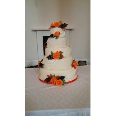 4 tier cake with drapes, delicate beading and hand made sugar flowers in bold colours of burnt orrange and deep purple