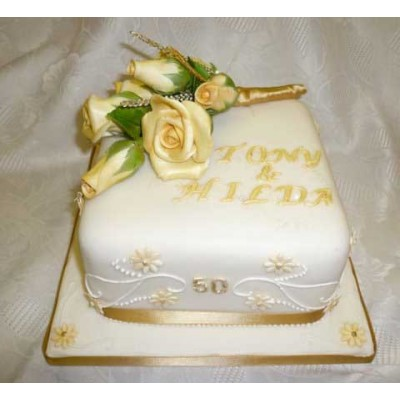 White and gold cake with golden flowers on top
