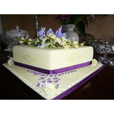 Purple ribboned cake with flower topper decoration